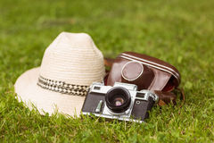 Vintage camera with his cover near a straw hat Stock Photo