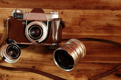 Vintage camera in leather case with lenses background Stock Photos