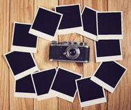 Vintage  camera and many blank photo frames on wooden table. Top Royalty Free Stock Photos