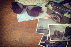 Vintage Camera and Map. Vintage camera, map, sunglasses and photo prints on wooden table with copy space Royalty Free Stock Photos