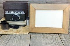 Retro camera, negative films, old photos and empty frame on grey. Vintage camera, negative films, old photos and empty frame on grunge wooden table Stock Photos
