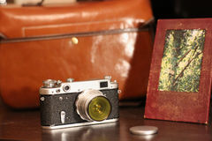 Vintage Camera next to the bag for photo equipment and photo frame. Vintage Camera next to a leather bag for photo equipment and leather photo frame Stock Images