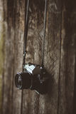 Vintage camera on old background of wood. An old black and silver analog camera hanged on the background of wood. The camera is in perfect shape, and zoom lens Stock Photo