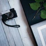 vintage camera, an old photo album on the white wooden table stock photography