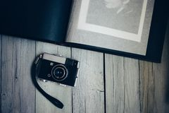 vintage camera, an old photo album on the white wooden table royalty free stock photo