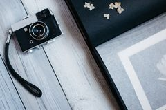 vintage camera, an old photo album on the white wooden table stock images