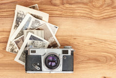 Vintage camera and old photos. On wooden background Royalty Free Stock Photos