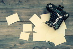 Vintage camera and old photos on wooden background. Retro style Stock Images