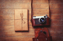 Vintage camera and package on wooden table. Stock Photography