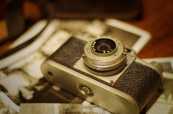 Vintage camera. Vintage photo camera with old pictures on wooden table Royalty Free Stock Image