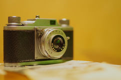 Vintage camera. Vintage photo camera with old pictures on wooden table Stock Photography