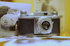 Vintage camera. Vintage photo camera with old pictures on wooden table Stock Images
