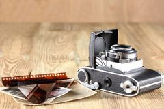 Old camera, photographic print and negative film on a wooden table with copy space royalty free stock images