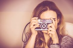 Vintage Camera Photography. Young Woman in Her 20s Taking Pictures Using Aged Vintage Photo Camera Royalty Free Stock Images
