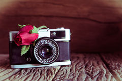 Vintage camera with roses on old wood background. Stock Photo