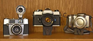 Vintage camera trio from three decades stock photography