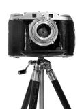 Vintage Camera on tripod. Vinatage Camera on tripod over white background Royalty Free Stock Images