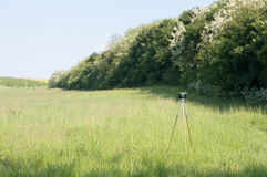 Vintage camera tripod on green meadow Royalty Free Stock Image