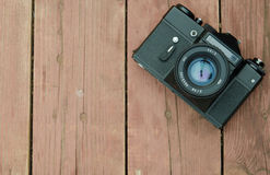 Vintage camera while wearing the Zenith Helios lens rests on a w. Retro camera on a wooden background Royalty Free Stock Images