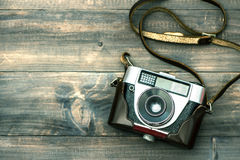 Vintage camera on wooden background. Retro style toned picture. Vintage camera on wooden background. Top view. Retro style toned picture royalty free stock photos