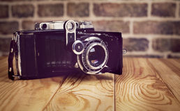 Vintage camera on wooden and brick  background Stock Photos