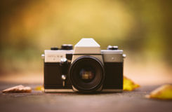 Vintage camera on a wooden desk in the park. Product photograph with shallow depth of field Stock Photography