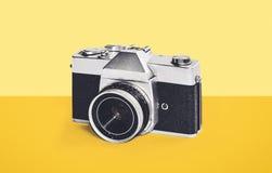 Vintage camera on yellow. Background Stock Photo