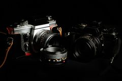 Vintage cameras and lenses on a black background. Vintage film cameras and lenses on a black background Stock Photography