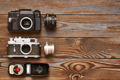 Vintage cameras and lenses on wooden background Stock Image