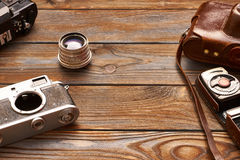 Vintage cameras and lenses on wooden background Royalty Free Stock Images