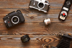 Vintage cameras and lenses on wooden background Royalty Free Stock Photo