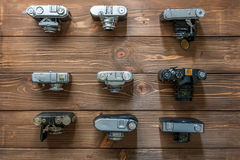 Vintage cameras and lenses on wooden background. At summer days Royalty Free Stock Image