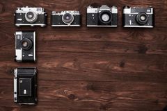 Vintage cameras lying vertical in the dark wooden flat area Stock Images