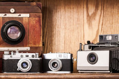 Vintage cameras on wooden background. Royalty Free Stock Photos