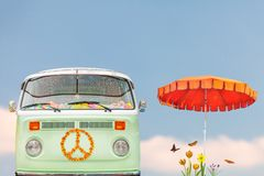 Vintage camper mobile home in two tone green and white with parasol. Flowers and butterflies stock photos