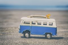Vintage Camper Toy with Surfing Boards on Beach. Blue vintage camper van toy with yellow surfing boards on sandy beach as holidays concept stock images