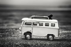 Vintage Camper Toy with Surfing Boards on Beach. Monochrome vintage camper van toy with yellow surfing boards on sandy beach as holidays concept royalty free stock image
