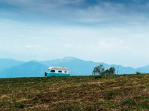 Vintage camper van stationary near a mountain meadow on a spring. Day, travel in the countryside and mountains stock images