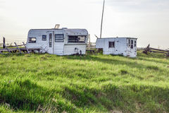 Vintage Campers Trailers. Old vintage camper trailers sitting in grassy field near wooden fence on an overcast day Stock Photos