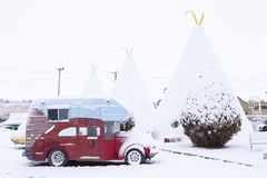 Vintage camping car parked in front of iconic concrete tipis of the 1937 Wigwam Motel under a layer of fresh snowClassic pale blue stock photo