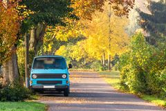 Vintage camping car on road with colorful autumn foliage trees. Blue retro camping car parking on residential road. Beautiful sunrise light and orange autumn royalty free stock photo