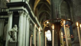 Vintage candelabrum in cathedral. Candelabrum in medieval cathedral. Close-up burning candles, people light one candle from another at background blurred stock footage