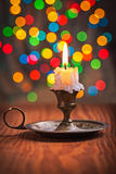 Vintage candle in candleholder on wooden board and background of Stock Photos