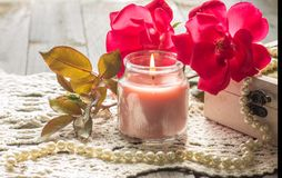 Vintage candle. A light pink candle with a vintage theme surrounded by beautiful pink roses Stock Photography