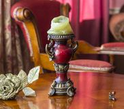 Vintage candlestick on the table next to an artificial rose and a hairpin in the idea of a butterfly. Classical interior royalty free stock photos