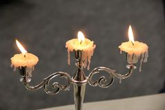 Vintage candlestick with three burning candles. Horizontal view royalty free stock photography