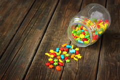 Vintage candy jar on wooden table. Vintage colorful candy jar on wooden table royalty free stock photography