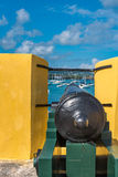 Vintage cannon through the turret facing the sailboats in the Ca. Ribbean Royalty Free Stock Photo