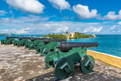Vintage cannons facing the Caribbean ocean defending the bay. 5 cannons in a row.  Small island in the background.  Blue sky with clouds Stock Image