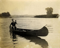 Vintage Canoe. Paddler. Circa 1909 print has many scratches, artifacts, fading, and solarization qualities Stock Photo